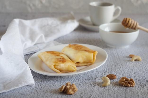 두 개의 팬케이크는 회색 테이블에 접시에 있습니다. 근처에는 꿀, 수건, 견과류가 있습니다. 아침밥