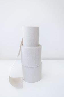 灰色のトイレットペーパーのロールが白いテーブルの上に立っています。衛生と清潔のコンセプト。