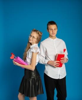 学童のカップルは、青い背景のバレンタインデーのティーンエイジャーです