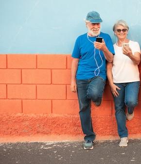イヤホンで携帯電話で話している壁に立っている年配の男性と女性のカップル。カジュアルな服。二人の笑顔とリラックス