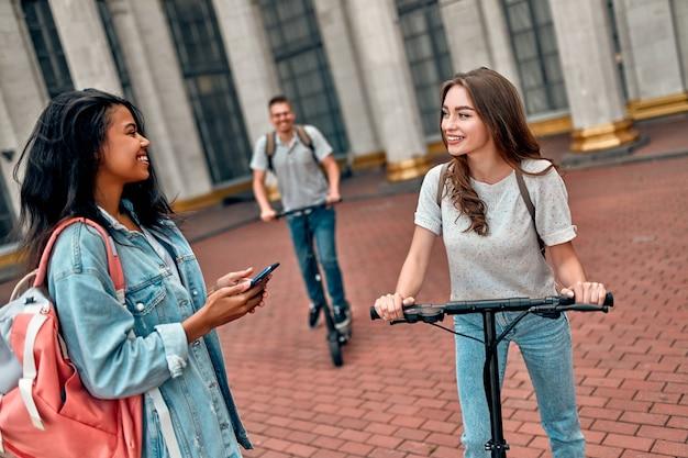 Пара студентов на электросамокатах встретила своего друга за пределами университетского городка.