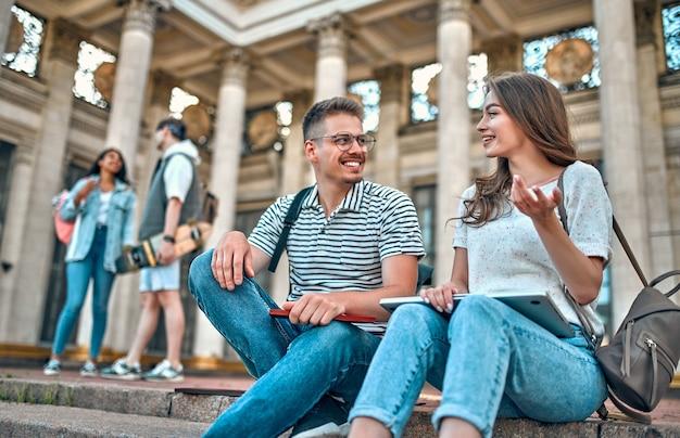Пара студентов с рюкзаками и ноутбуком сидят на ступеньках возле кампуса и разговаривают.