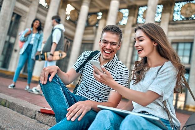 Пара студентов с рюкзаками и ноутбуком сидят на ступеньках возле кампуса. девушка что-то показывает парню на своем смартфоне.