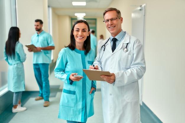 聴診器と患者カードを持った数人の成功した常勤の医師がクリニックの廊下に立ち、バックグラウンドで医療チームと治療について話し合っています。
