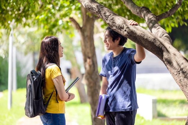 Пара тайских старшеклассников улыбаются, идя по лесу с книгой в руках, парень и девушка на улице.