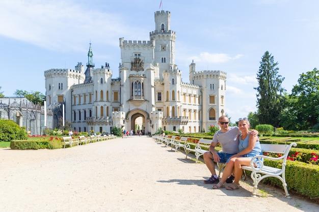 Пара туристов сидят на скамейке перед прекрасным замком глубока-над-влтавой - чехия.