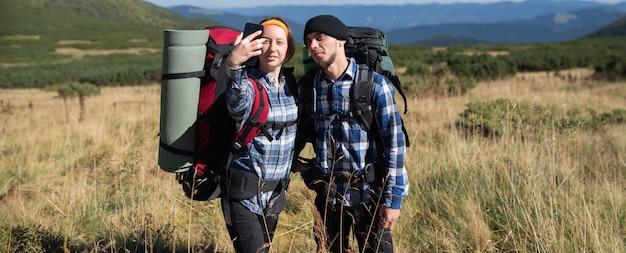恋をしている二人の観光客、男と女が山の平原に立ち、スマートフォンで自分撮り