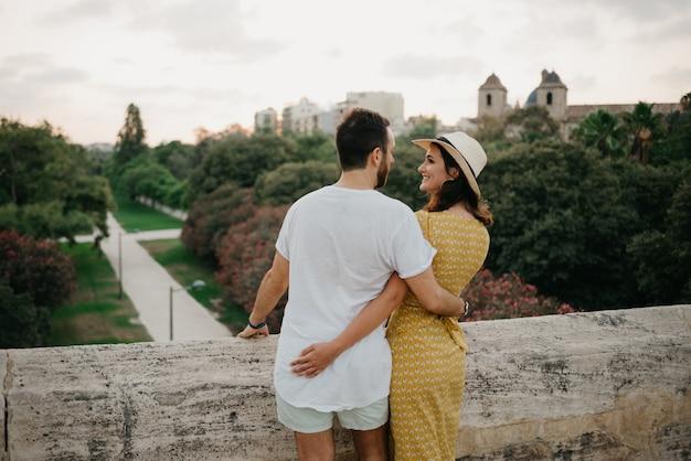 Пара туристов смотрят друг на друга в парке вечером в валенсии.