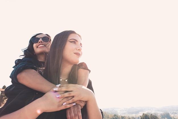 晴れた日の間に抱き合って楽しんでいる2人の女性