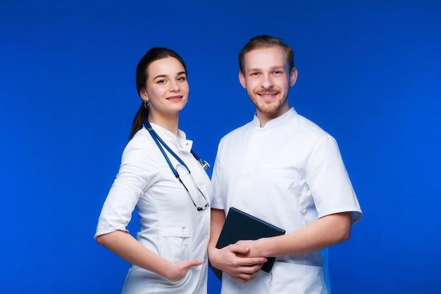 흰 가운을 입은 두 명의 젊은 의사, 남자와 여자가 파란색 배경에 미소를 짓고 있습니다.
