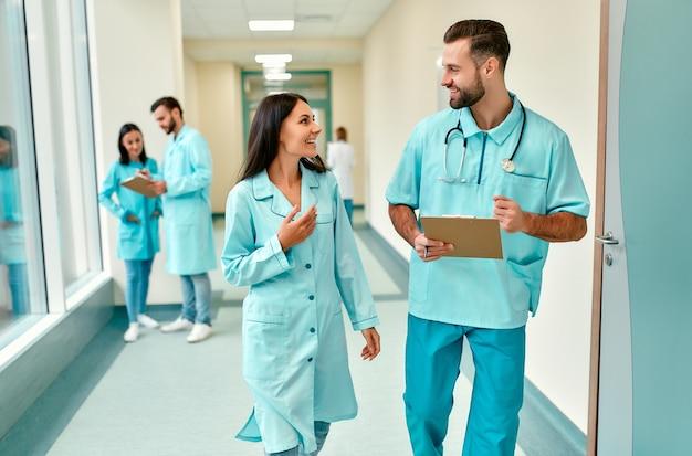 聴診器と患者カードを持った数人の若い医師がクリニックの廊下を歩き、治療方法について話し合います。