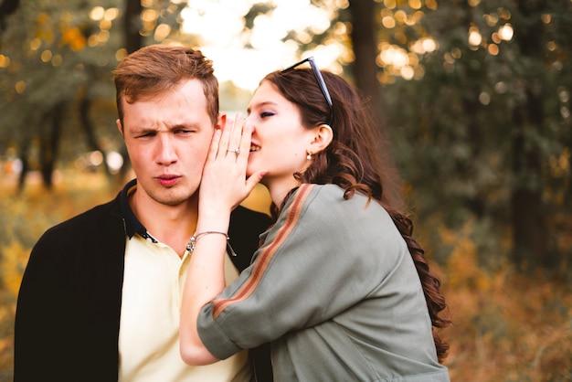 若い男と女のカップルがお互いに秘密を告げ、耳元でささやきます