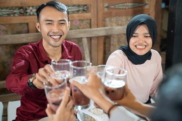 Пара молодых людей празднуют и поднимают бокалы с фруктовым льдом для тостов, прерывая пост ...