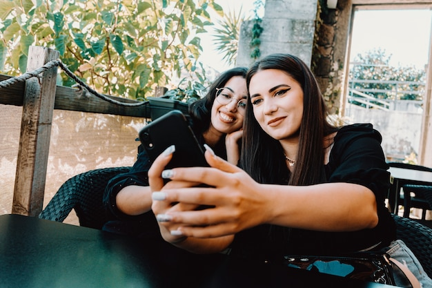 笑顔でバーで自撮りを取る若い女性のカップル
