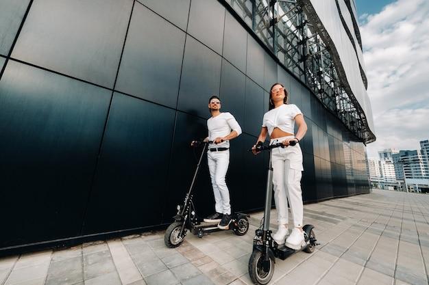 Пара на электросамокатах катается по городу, влюбленная пара на скутерах.