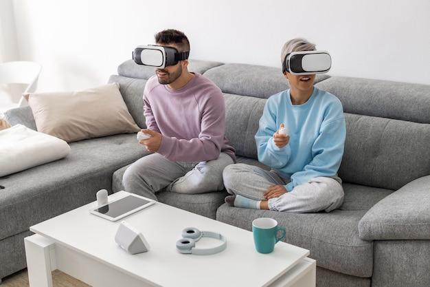 カップルは、リビングルームのソファでバーチャルリアリティメガネをかけてバーチャルリアリティでゲームをします。