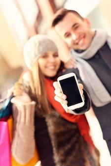 ショッピング中にスマートフォンを示すカップル