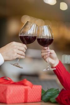 レストランに座ってワイングラスを渡ったカップル。ギフトボックスとテーブルの上の美しいバラ。カフェでワインを飲んでいる男女。バレンタインデーのコンセプト。