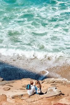 岩の上に座って、アメリカのサンディエゴの海を見ているカップル