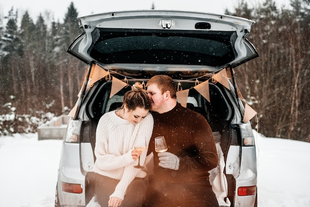 車の後ろにカップを持って座って、雪の森でピクニックをしているカップル