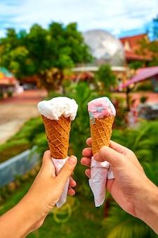 Пара фотографирует рожки мороженого в руках.