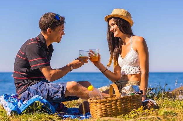 Пара тостов из многоразовых стаканов с апельсиновым соком в горах у моря, наслаждаясь жарой