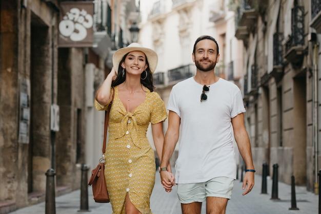 Пара, идущая в старом городе испании. парочка туристов на свидании в вечерней валенсии.