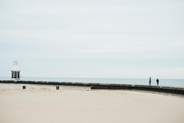 イリノイ州シカゴで砂と湖と橋を歩いているカップル。