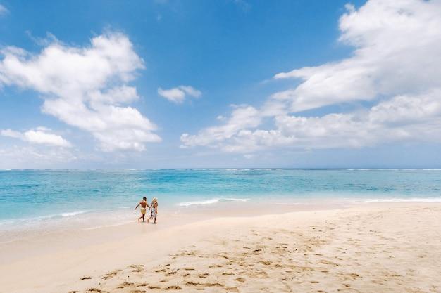 한 커플이 인도양의 모리셔스 해변을 따라 걷고 있습니다. 모리셔스의 열대 섬에 있는 청록색 물이 있는 해변의 최고 전망. 항공 사진,
