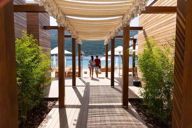 Пара идет по деревянной террасе через пляжное кафе к адриатическому морю.