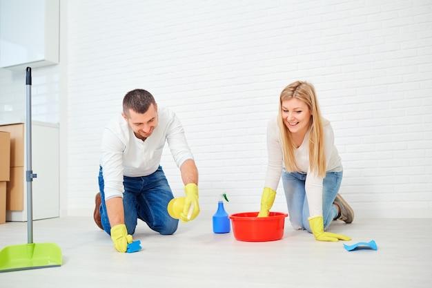 한 커플이 흰 벽에 바닥을 닦는다.