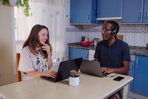 Пара работает дома со своими ноутбуками многонациональная пара смотрит друг на друга