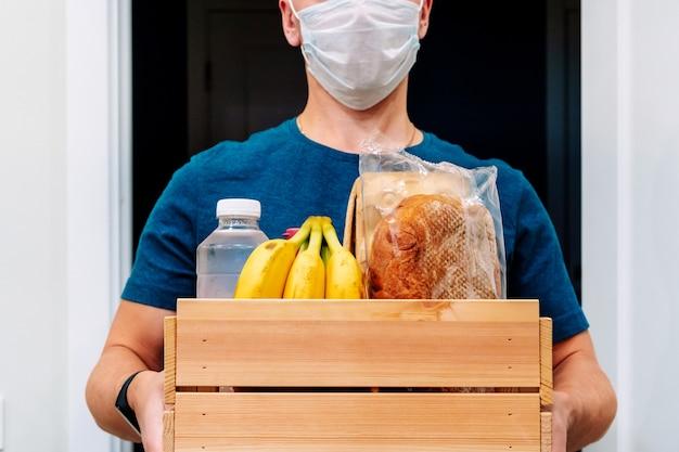 Курьер в маске доставляет ящик с продуктами. оказание услуги в условиях карантина