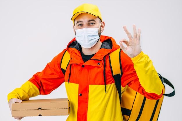 医療用マスクを着た宅配便が黄色いジャケットを着て自宅やオフィスに食べ物を配達し、背中の後ろにある断熱バッグに既製の食品が入った段ボール箱を入れて、ジェスチャーでokサインを示します
