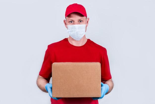 Курьер в красной форме и защитной медицинской маске и перчатках держит картонную коробку. безопасная бесконтактная доставка заказов в карантине