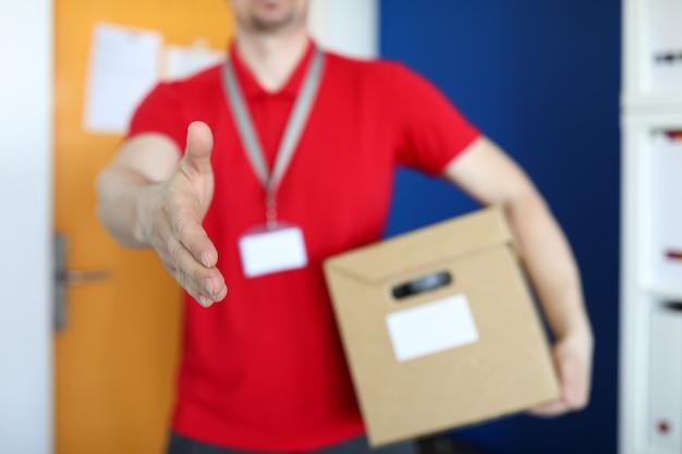制服の宅配便とバッジが小包を保持
