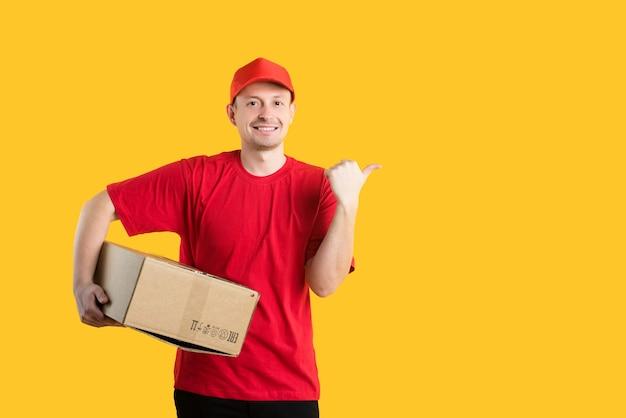 赤いtシャツと帽子をかぶった宅配便の男性が段ボール箱を手に持って黄色の指を見せています