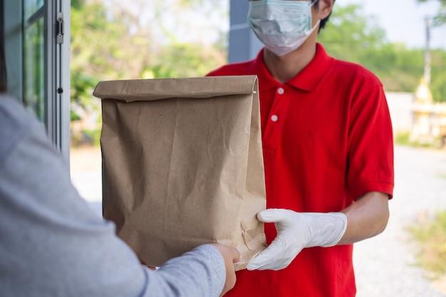 顧客の手に食品を届ける際の汚染のリスクを防ぐために、手袋とフェイスマスクを備えた赤いユニフォームを着た宅配便業者。フードデリバリーサービス