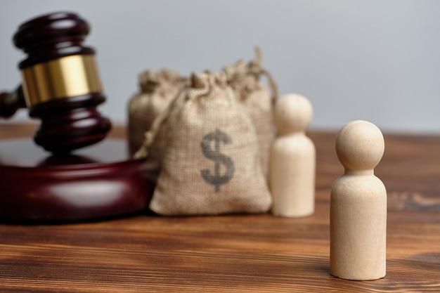 Судебное заседание между бизнесменами. абстрактные мешки с деньгами и фигурки людей рядом с судьей молотком.