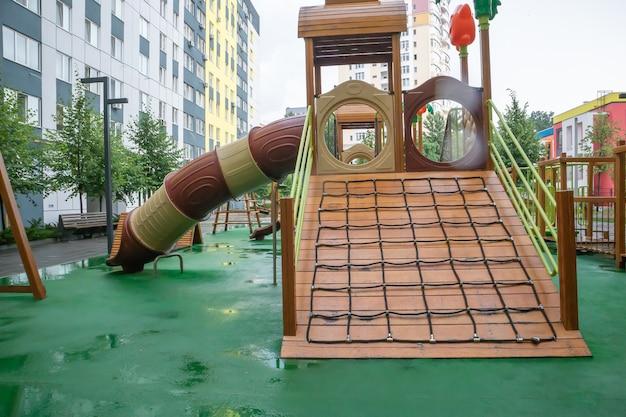 人のいない雨の夏の日に木とプラスチックで作られたモダンで広い遊び場がある高層ビルの中庭。空の屋外の遊び場。子供のゲームやスポーツのための場所。