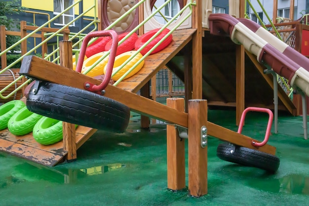 雨の夏の日、人のいない木とプラスチックで作られたモダンで広い遊び場のある高層ビルの中庭。空の屋外の遊び場。子供のゲームやスポーツのための場所。