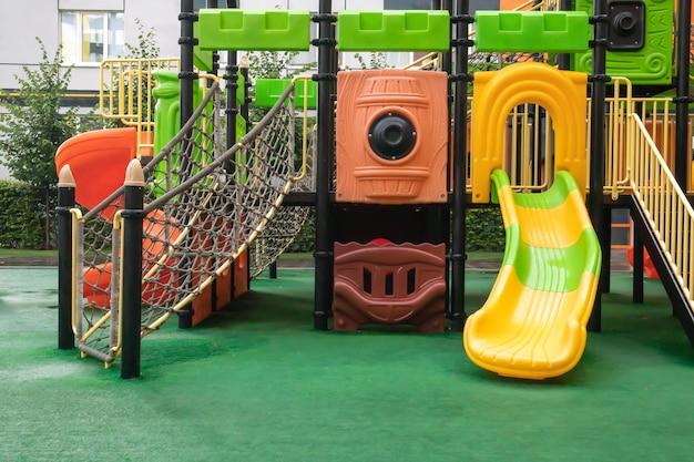 人のいない雨の夏の日に、新しいモダンでカラフルで広い遊び場がある高層ビルの中庭。空の屋外の遊び場。子供のゲームやスポーツのための場所。