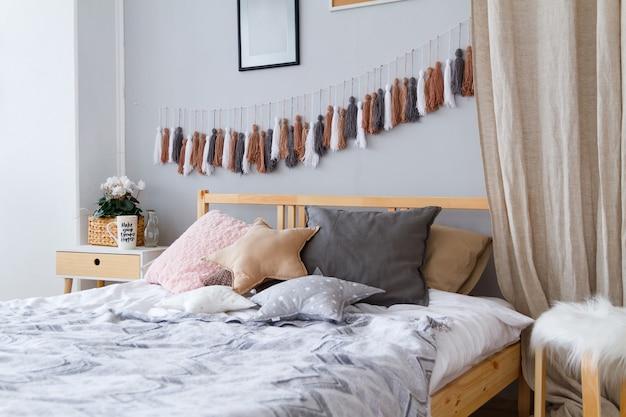 Уютная кровать с подушками и одеялами в светлой просторной спальне.