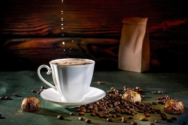 ストロベリーケーキ、香り高いホットコーヒー、チョコレートの居心地の良い朝食。クラフトパケットのテーブルの上の緑色のテーブルクロスで、コーヒー豆が目覚めました。