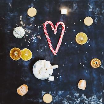 黒の背景の上面図にマシュマロキャンディケインオレンジと装飾が施された居心地の良いマグカップ