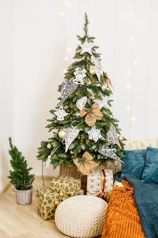 花輪とクリスマスツリーで飾られた居心地の良い部屋。白い枕ベッドはスタイリッシュでモダンです。良い新年の精神。テキストの明るい色の背景テクスチャの場所。休日の寝室の装飾