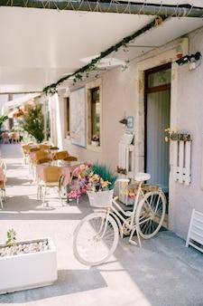Уютный белый зал кафе со столиками для посетителей и декоративный велосипед, украшенный цветами у входа.