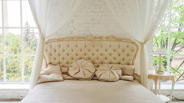 방에 아름다운 커튼이 달린 큰 창문 근처에 있는 아늑한 흰색 나무 침대. 대형 침대가 있는 흰색 스튜디오 인테리어에 우아한 조명이 있는 금색 프레임의 현대적인 커피 테이블입니다.