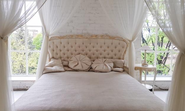 Уютная белая деревянная кровать у большого окна с красивыми шторами в комнате. современный журнальный столик в золотой оправе с элегантным светом в белом интерьере студии с большой кроватью.