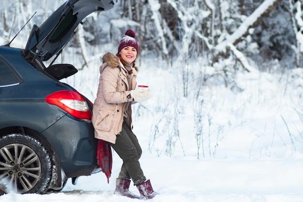 居心地の良い女性が微笑む、暖かい冬の服を着た女性が温かい飲み物、お茶、コーヒーを飲み、車のトランクに座って微笑む。休暇、車での旅行、雪の寒さ。コピースペース